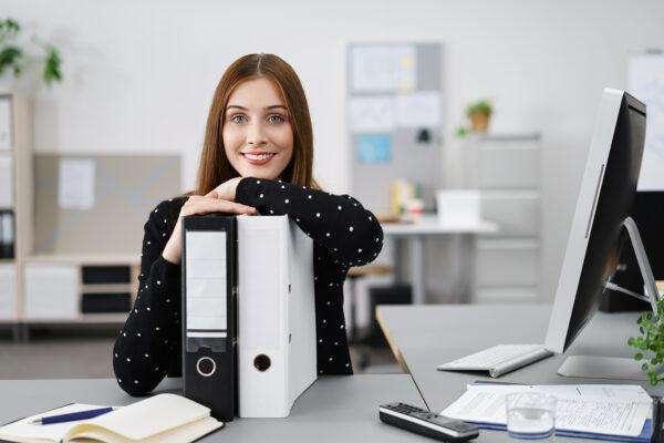 Lächelnde Frau Im Büro Stützt Sich Auf Aktenordner