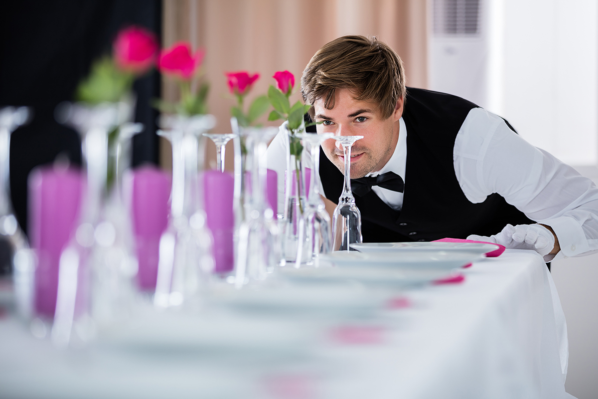 Waiter Looking At Table Arrangement